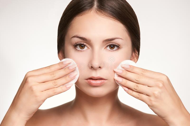 Cosmetic face makeup remove from skin. Clean care for beauty girl with cotton pad stock images