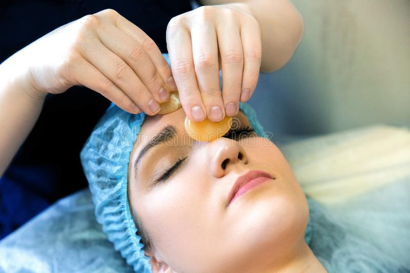 Cosmetic facial massage. Treatment of the skin with a semiprecious stone. Facial massage yellow nevritom. Cosmetic facial massage. Treatment of the skin with a stock photography