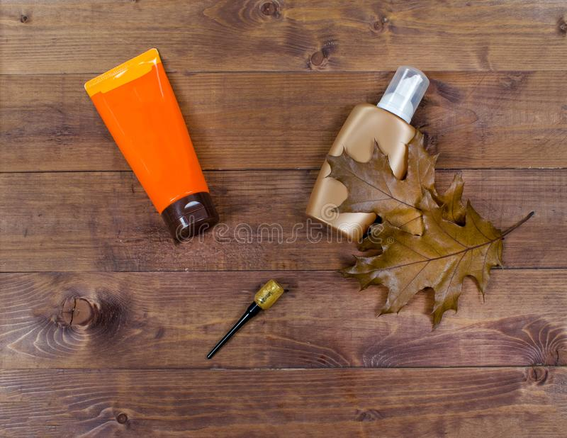 Cosmetic flatlay with beauty products, eyeliner and leaves on a wooden background. stock images