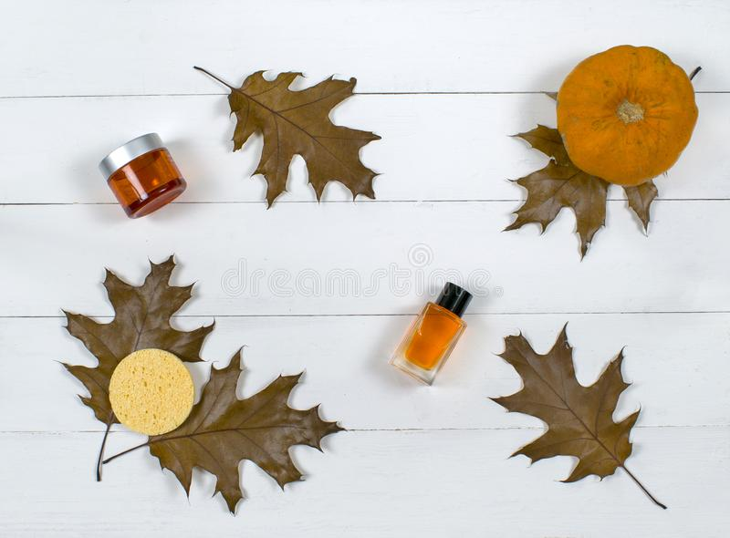 Cosmetic flatlay with beauty products, sponge and pumpkin with leaves on a wooden background. royalty free stock image