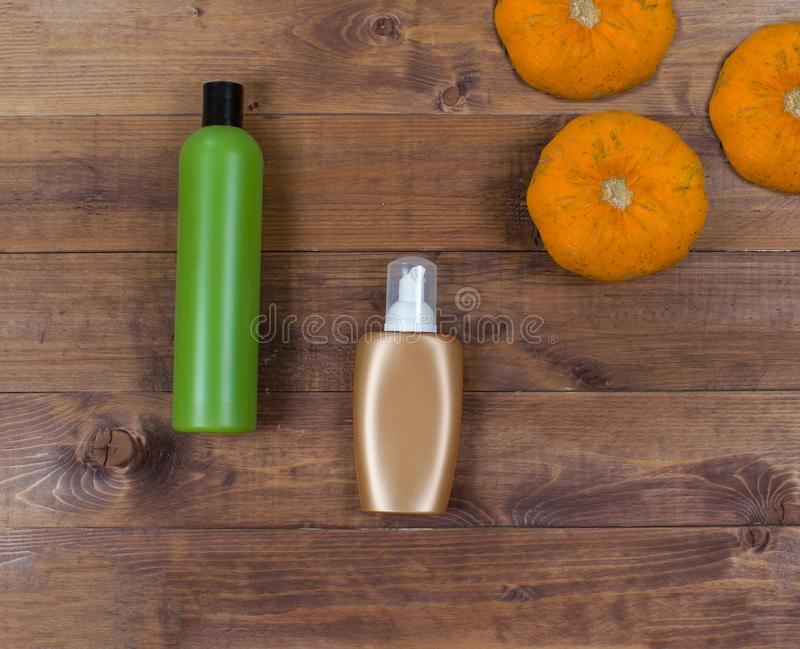 Cosmetic flatlay with beauty products and pumpkins on a wooden background. stock photography