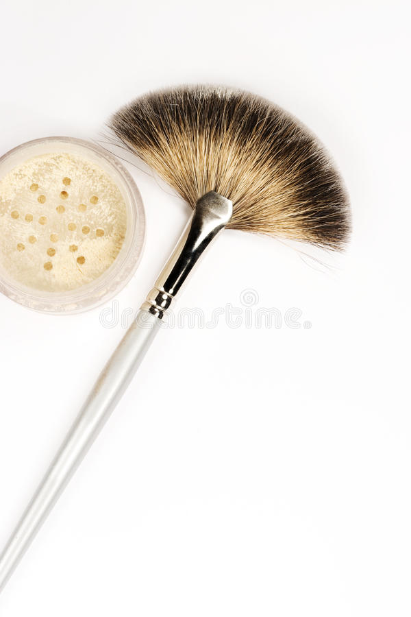 Cosmetic Fan Brush Powder. A natural bristle cosmetic fan brush and container of powder resting on white background stock photos