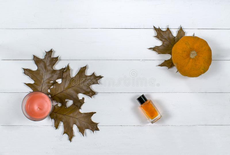 Cosmetic flatlay with beauty product, candle and pumpkin with leaves on a wooden background. royalty free stock image