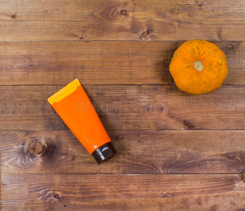 Cosmetic flatlay with beauty product and pumpkin on a wooden background. stock images