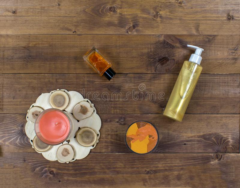 Cosmetic flatlay with beauty products, bottle, scrub and candle on a wooden background. royalty free stock photos