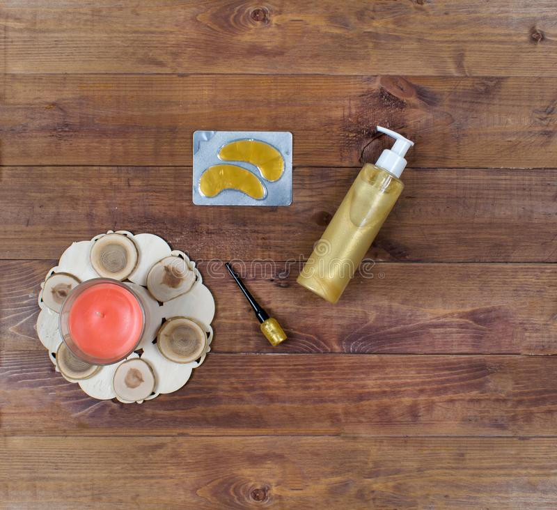 Cosmetic flatlay with beauty products, patches, cream, eyeliner and candle on a wooden background. royalty free stock images