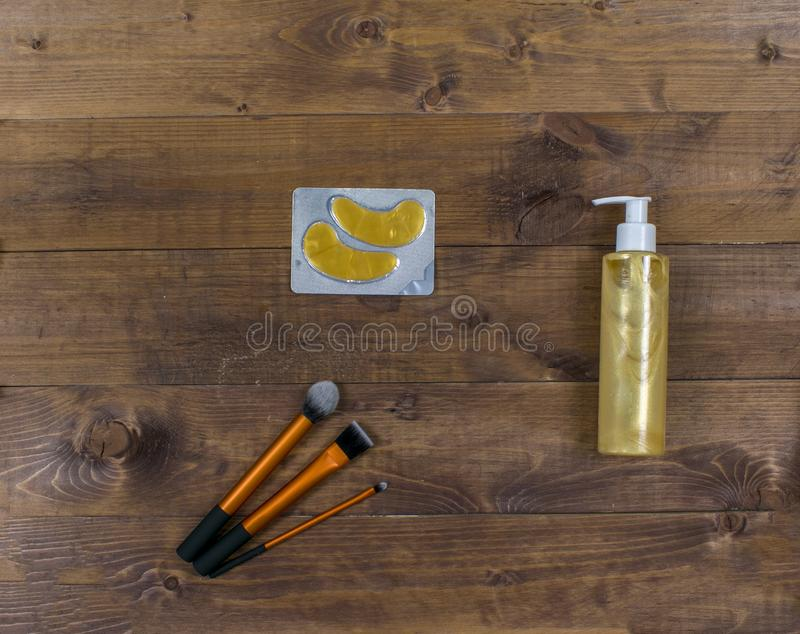 Cosmetic flatlay with patches, brushes, cream and eyeliner on a wooden background. royalty free stock photo