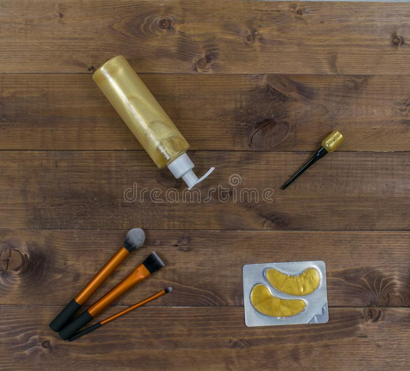 Cosmetic flatlay with patches, brushes, cream and eyeliner on a wooden background. stock photo