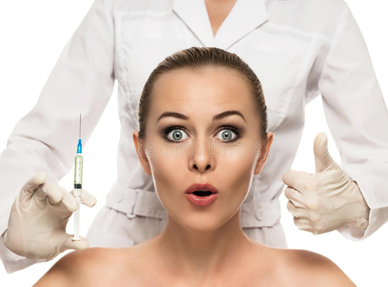 Cosmetic injection to the pretty Beautiful woman face and beautician hands with syringe. Doctor woman giving botox injections. Isolated on the white background royalty free stock photo
