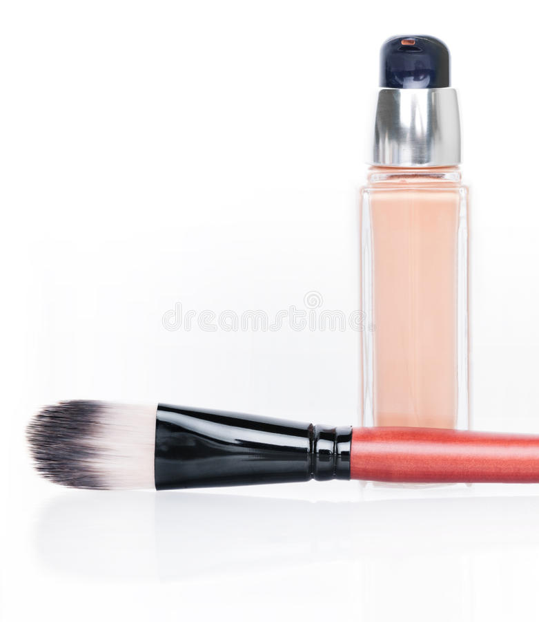 Cosmetic liquid foundation and brush on white stock images