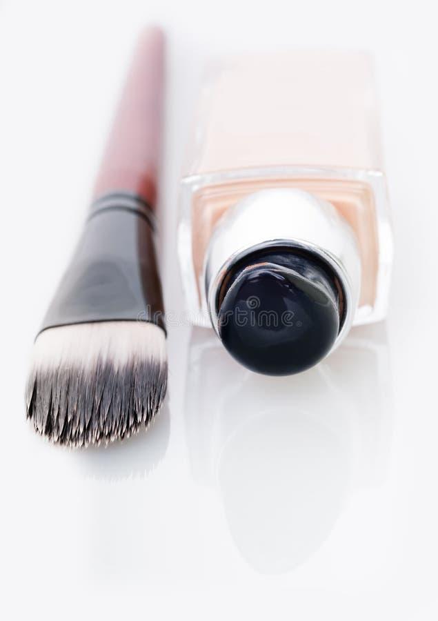 Cosmetic liquid foundation and brush on white stock photo