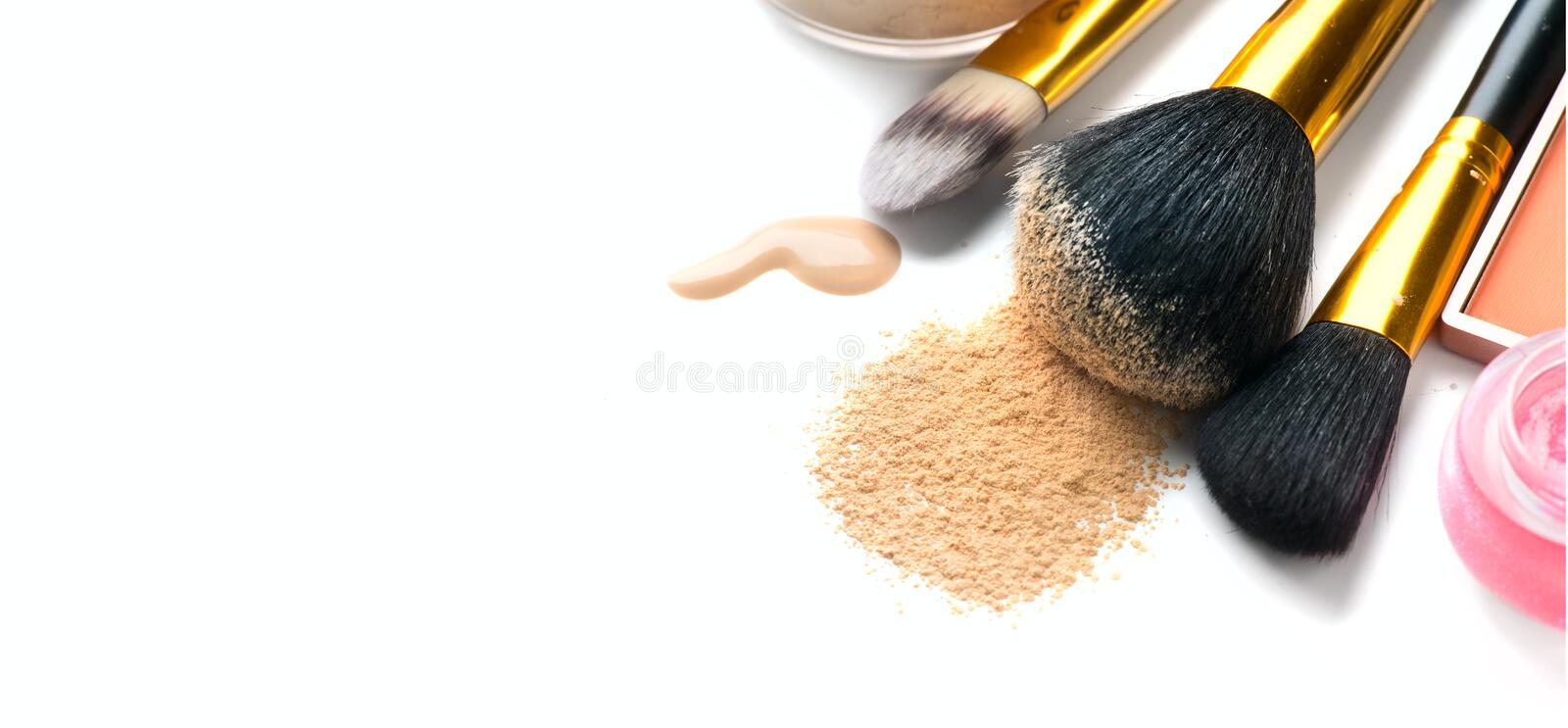 Cosmetic liquid foundation or cream, loose face powder, various brushes for apply makeup. Make up concealer smear and powder stock photos