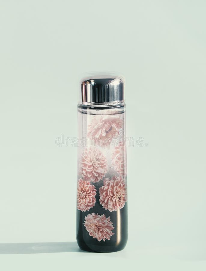 Cosmetic liquid product bottle with flowers essence or toner on light mint background, front view. Beauty product concept. Blank label for branding mock-up royalty free stock photo