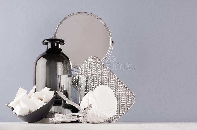 Cosmetic and make up accessories and home decoration black glass vase, silver mirror, bowls on soft white wood table. stock images
