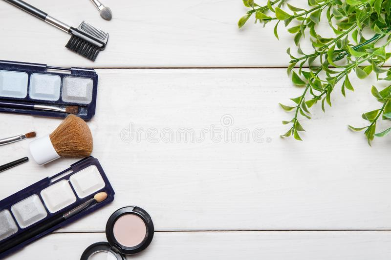 Cosmetic makeup items and green plant branch on a white wooden table, flat lay template with text space in the middle royalty free stock image