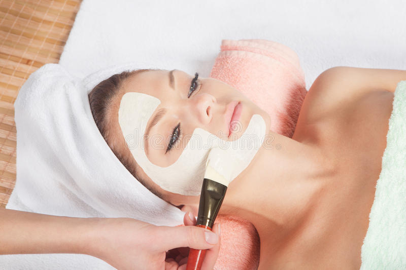Cosmetic mask at spa salon. Beautiful young woman having a facial cosmetic treatment stock photo