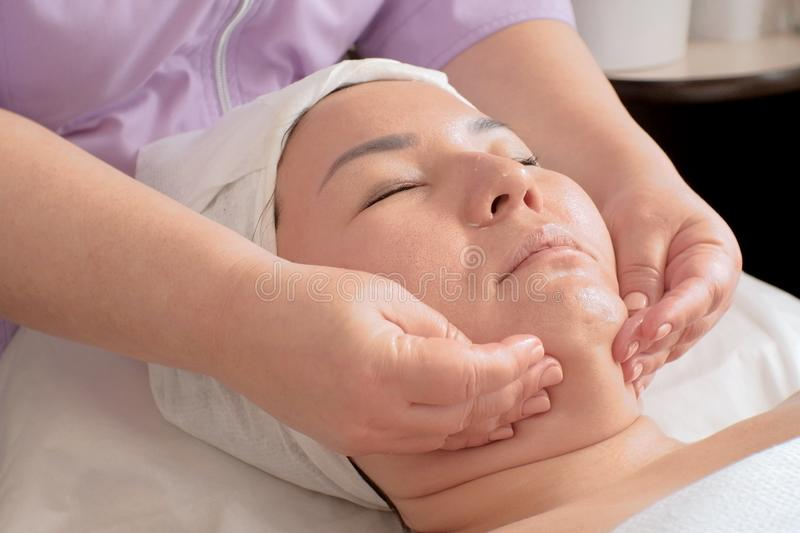 Cosmetic massage against the second chin. The technician is massaging female face at beauty salon. Spa procedures. Relaxation stock images