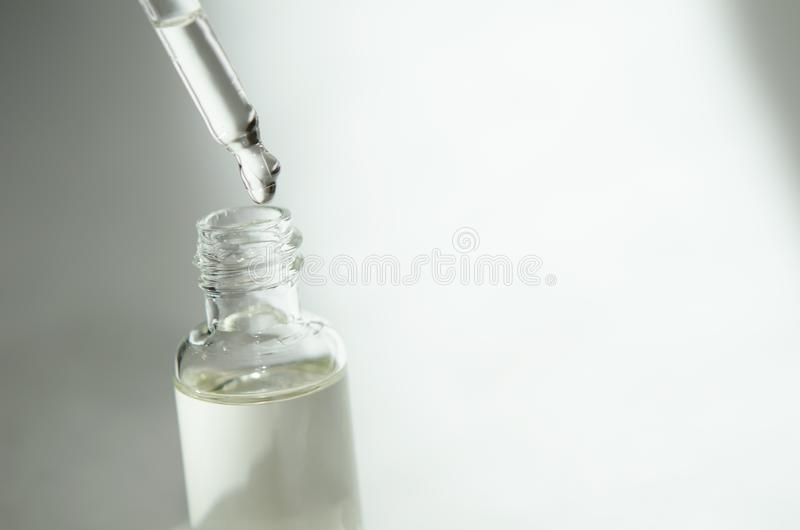 Cosmetic or medical glass bottle with pipette on white background. Skin care concept. Natural hard light, deep shadows. stock image