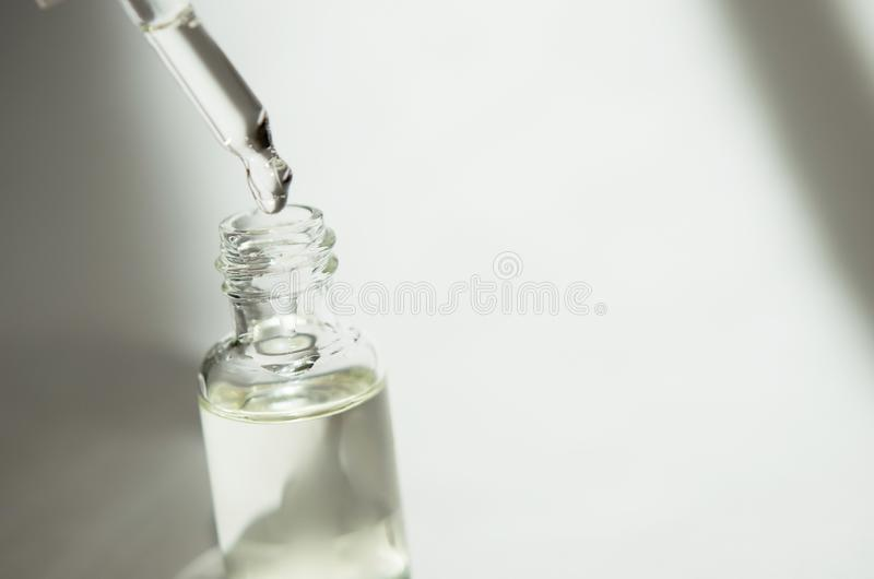 Cosmetic or medical glass bottle with pipette on white background. Skin care concept. Natural hard light, deep shadows. royalty free stock photography
