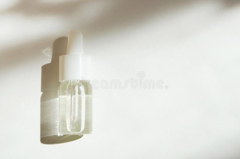 Cosmetic or medical glass bottle with pipette on white background. Skin care concept. Natural hard light, deep shadows. royalty free stock photo