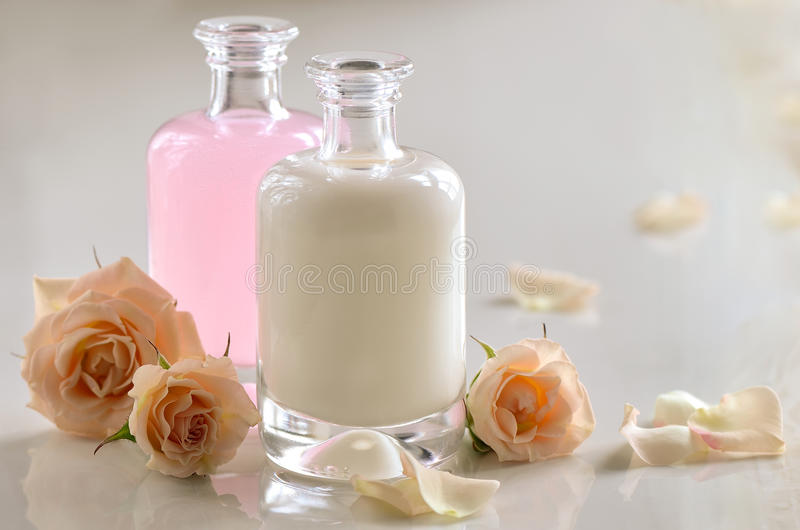 Cosmetic milk and toner. Cosmetic liquids, maybe milk, shampoo or toner, in glass bottles decorated with roses royalty free stock image
