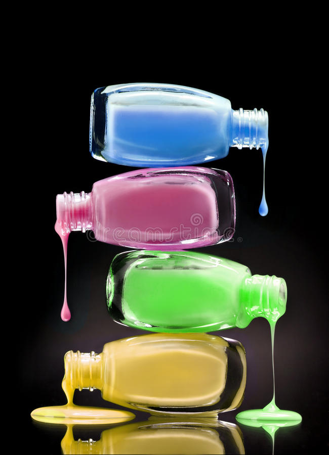 Cosmetic nail polish dripping from open bottles on black background. royalty free stock image