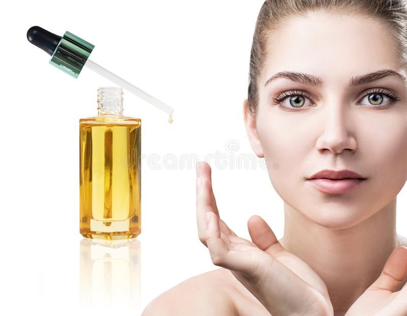Cosmetic oil applying on face of young woman. royalty free stock image