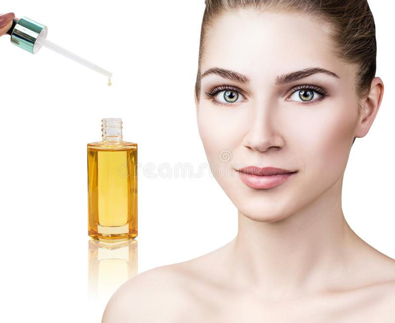 Cosmetic oil applying on face of young woman. royalty free stock photography