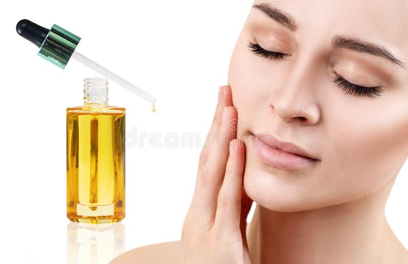 Cosmetic oil applying on face of young woman. stock photography