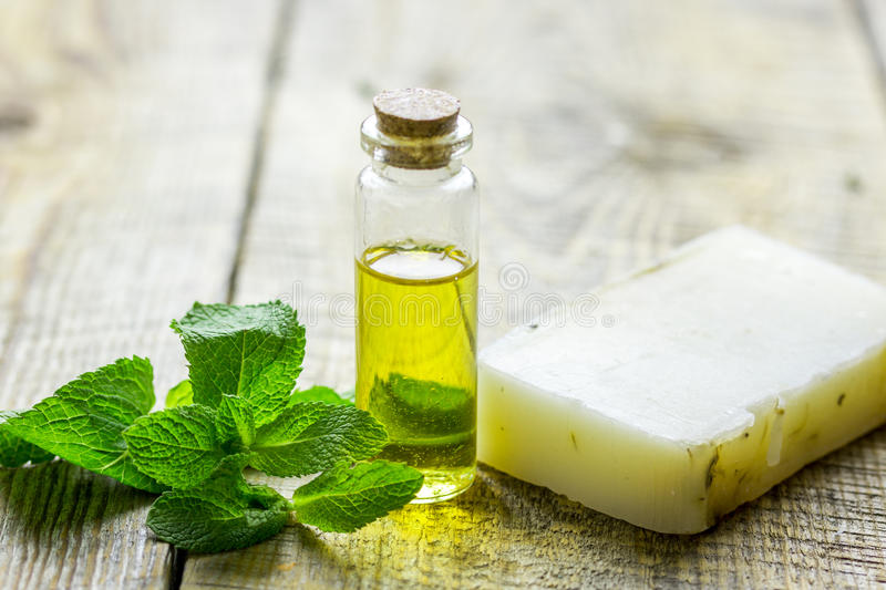 Cosmetic oil in bottle and soap with herbs on light table background stock photo