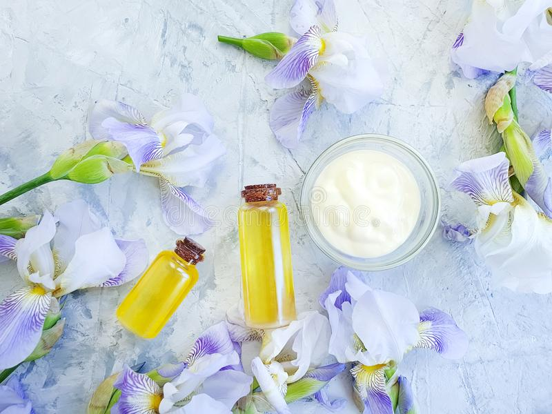 Cosmetic oil, cream, natural flower protection ointment iris essence on a gray concrete background royalty free stock image