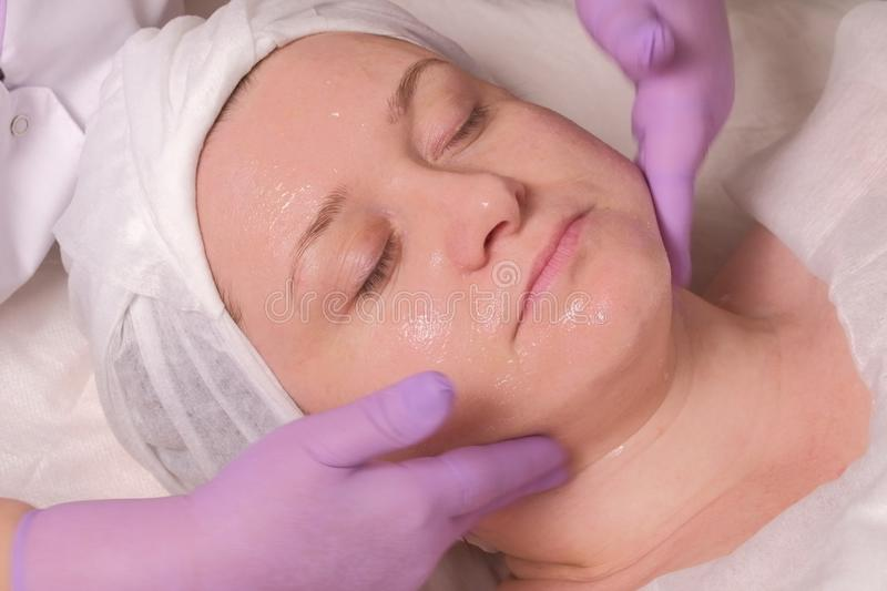 Cosmetic procedure. Facial massage with a transparent gel. Woman with eyes closed. Beautician hands in pink gloves. Concept of stock image