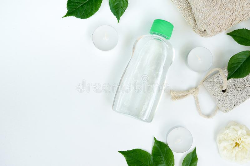 Cosmetic product bottle with micellar water or tonic for skin care, green leaves, white background with copy space, front view. stock photography