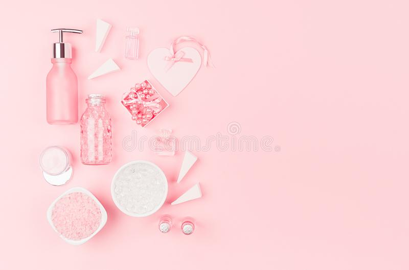 Cosmetic products and accessories in pink color - cream, bath salt, essential oil, soap, towel,  pearls, bottles, heart, bowl. stock photography