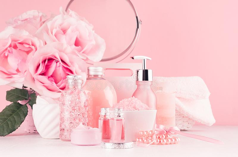 Cosmetic products for aromatherapy, spa salon - essential rose oil, bath salt, cream, soap, bath accessories with round mirror. royalty free stock photo