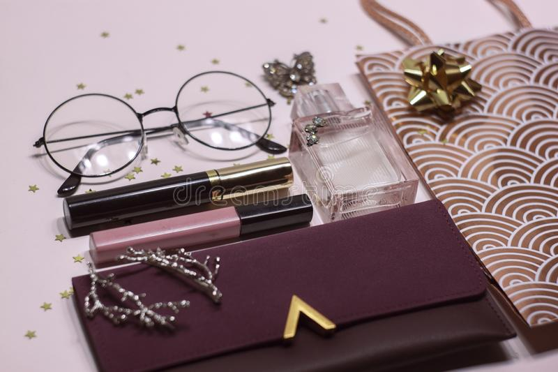 Cosmetic set: glass, perfume, handbag, mascara and lip gloss. Colorful women`s cosmetic set: glass, perfume, handbag, mascara and lip gloss on pink background royalty free stock images