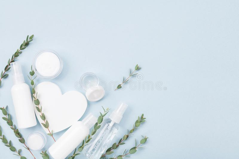 Cosmetic set for skin care and beauty treatment decorated with white wooden heart and eucalyptus leaves top view. Flat lay. royalty free stock photo