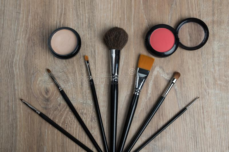 Cosmetic set of various shades compact and loose face powder, concealer and makeup brush. stock photography