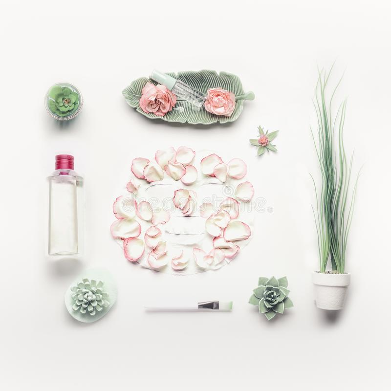 Cosmetic setting for facial skin care with sheet mask , pink roses and roses water, essence or toner on white background. Top view, place for text. Beauty and royalty free stock photo