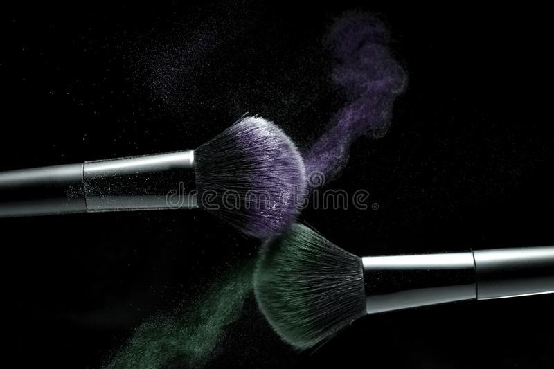 Cosmetic shades of different colors, lilac and green, fly away from two makeup brushes creating a fancy pattern on a black stock image