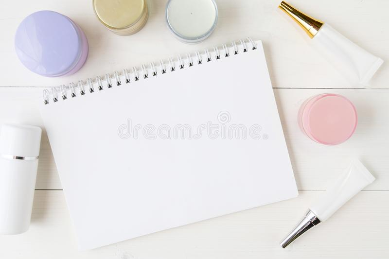 Cosmetic and skin care product and notebook on white wood table, beauty with treatment cream and moisturizer and notepad copy spac. E on wooden desk, health and stock photo