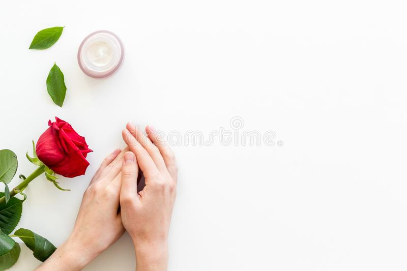 Cosmetic spa set with rose flowers and cream for body in hands on white desk background top view mock-up stock image