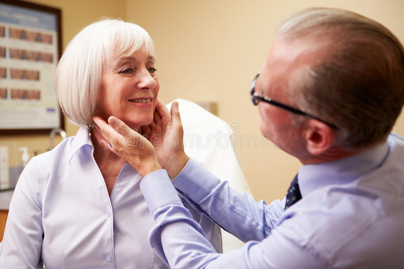 Cosmetic Surgeon Examining Senior Female Client In. Office Looking At Each Other stock photography