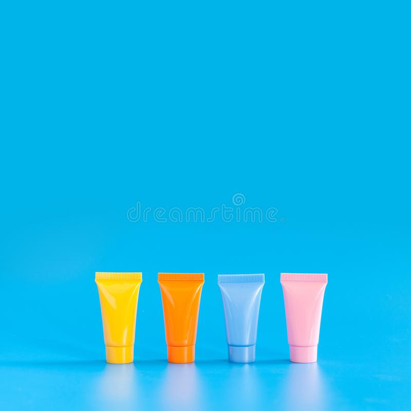 Cosmetic tubes on blue background. Yellow orange blue pink color abstract plastic containers, hygiene products packaging. Design poster template. Copy space stock photos