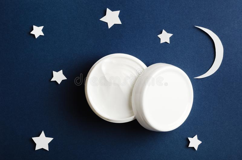Cosmetic white container on night sky background top view. Skincare cosmetology product, night care concept. Organic cosmetics. royalty free stock images