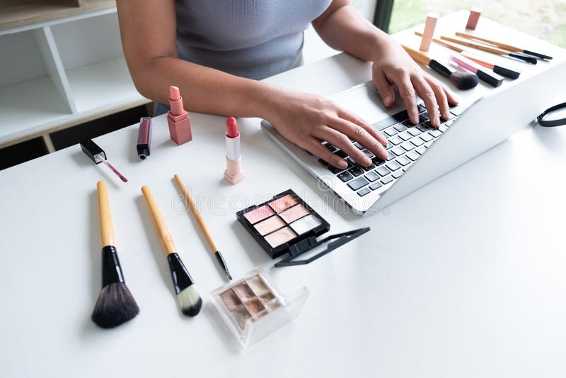 Cosmetici attuali di bellezza di blogger di bellezza che si siedono in compressa anteriore Il bello esame dei cosmetici di uso de fotografie stock libere da diritti