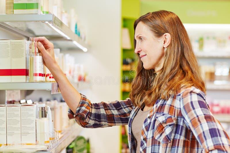 Cosmetici d'acquisto della donna anziana in farmacia fotografia stock libera da diritti