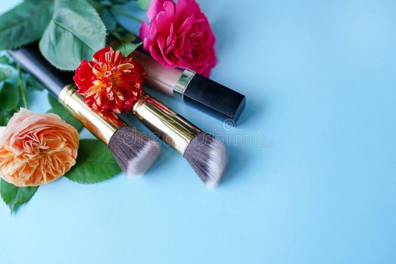 Cosmetici decorativi con i fiori rossi e rosa su fondo blu, spazio della copia fotografie stock libere da diritti