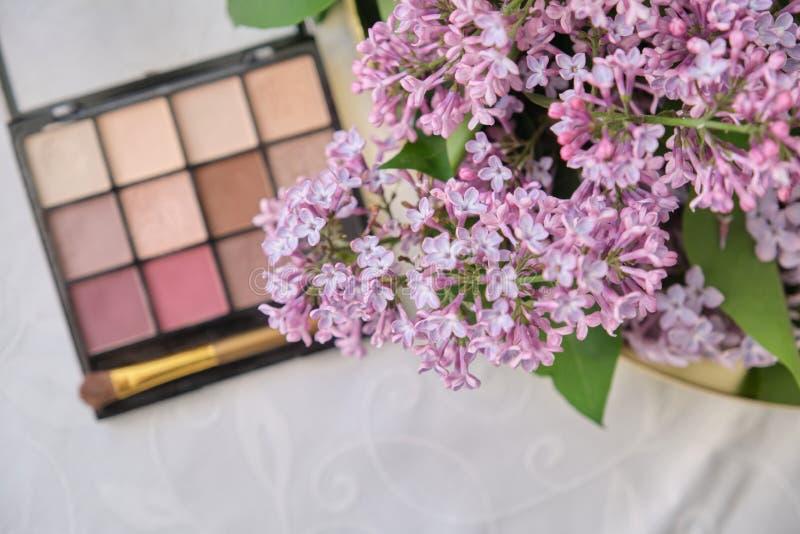 Cosmetici decorativi di trucco, ombretto con la spazzola e fiori lilla freschi immagini stock libere da diritti