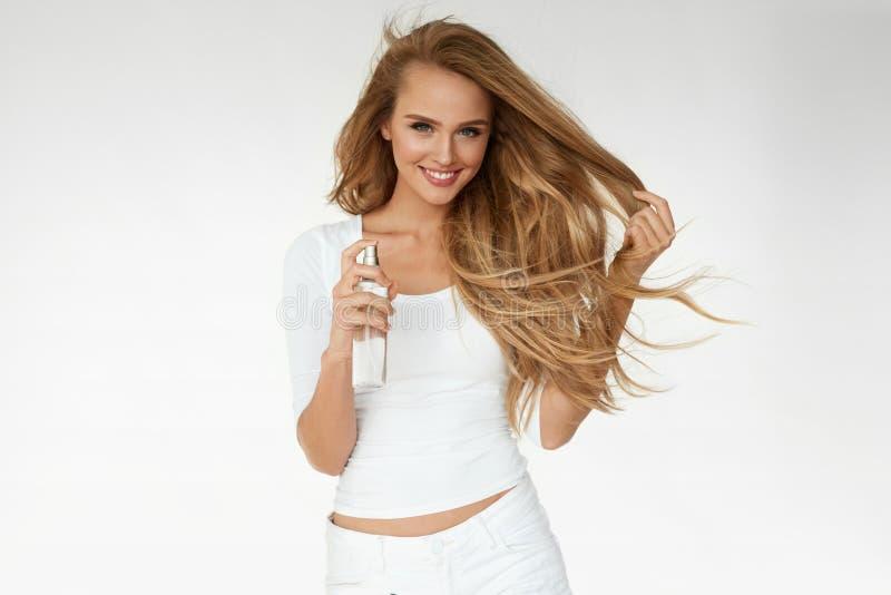 Cosmetici dei capelli Donna che applica spruzzo su bei capelli lunghi fotografia stock